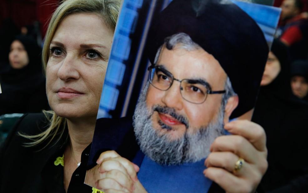 Mulher exibe foto do líder do Hezbolahh, Hassan Nasrallah, durante seu pronunciamento na TV libanesa, em Beirute, na sexta-feira (10) (Foto: AP Photo/Bilal Hussein)