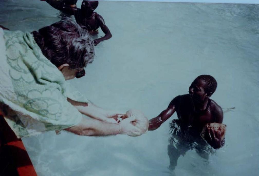 TN Pandit entrega um coco para um membro da tribo sentinela — Foto: TN Pandit/BBC