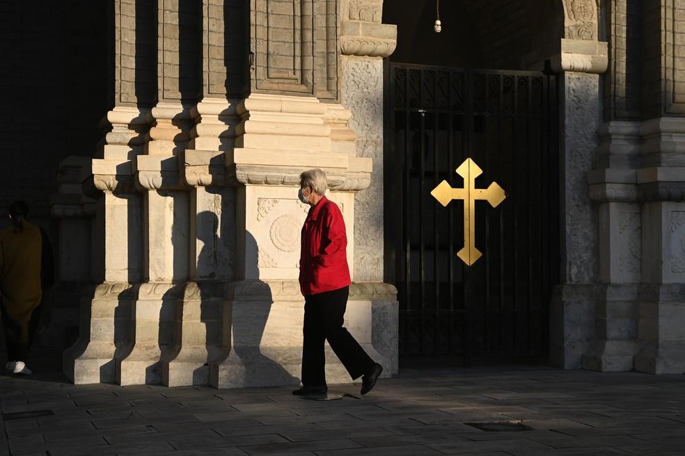 Uma mulher passa pela Igreja Católica Wangfujing, em Pequim, nesta quinta-feira (22) — Foto: Greg Baker/AFP