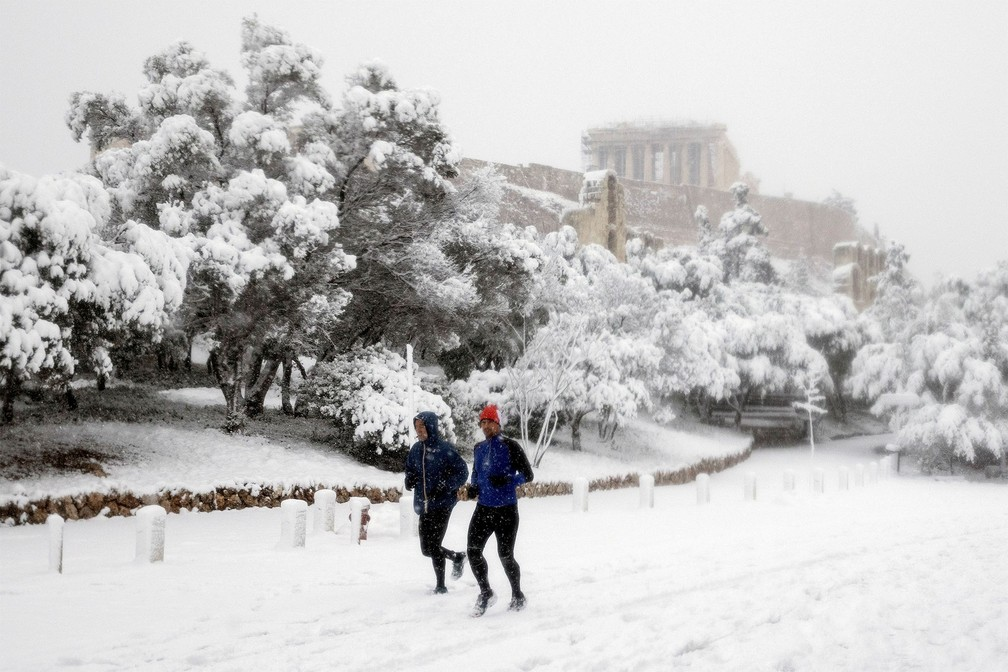 Dupla pratica corrida na neve com a Acrópole ao fundo em Atenas, na Grécia — Foto: Alkis Konstantinidis/Reuters