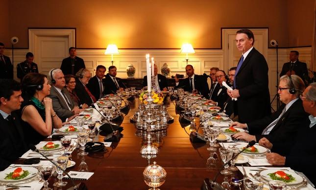 Jair Bolsonaro faz discurso em jantar com integrantes do governo e nomes da direita na embaixada do Brasil em Washington, em março. Bannon está sentado ao seu lado