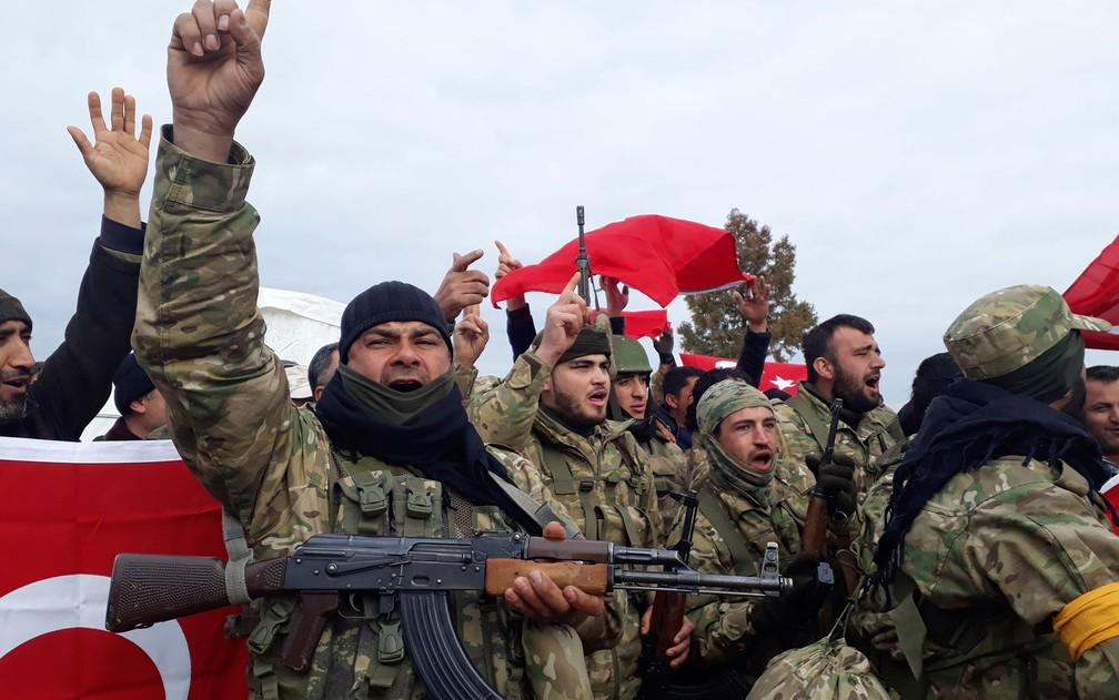 -  Soldados do Exército Sírio Livre, apoiados pela Turquia, soltam gritos de guerra antes de se dirigirem à fronteira com a Síria, em Kirikhan, na Turqu