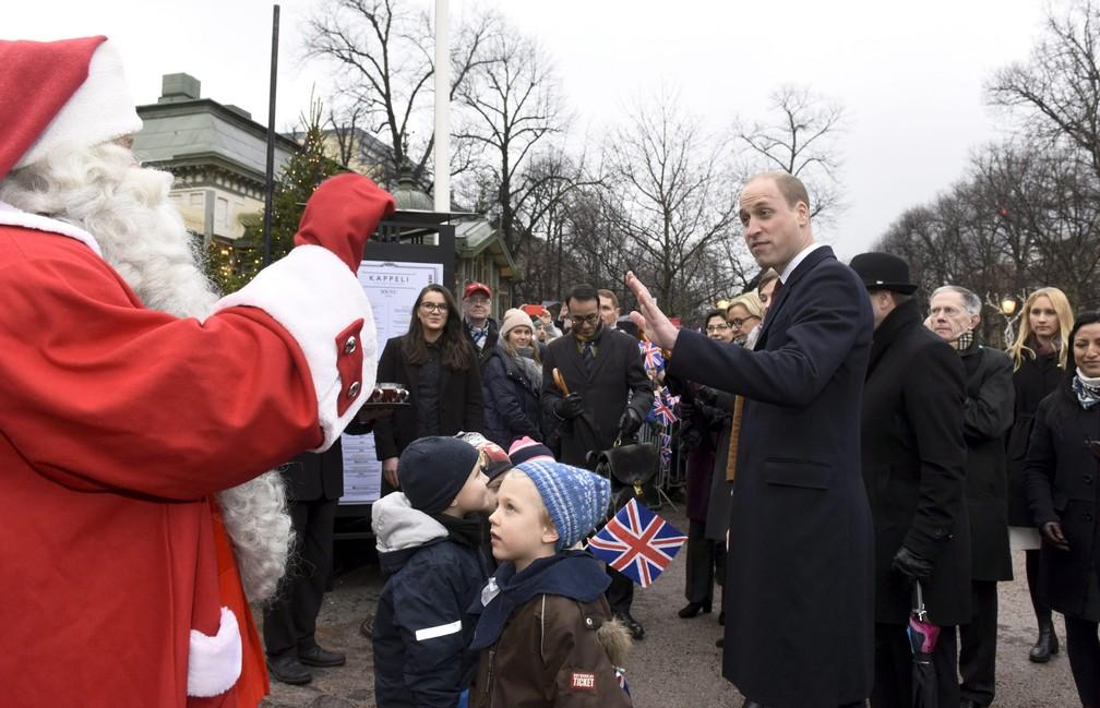 Príncipe William cumprimenta homem vestido de Papai Noel nesta quinta-feira (30) em um parque de Helsinki (Foto: Heikki Saukkomaa / Lehtikuva/ AFP)