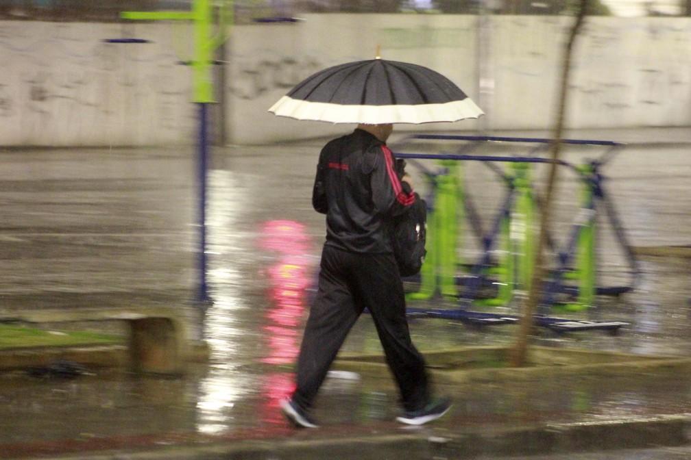 Pedestre se protege da chuva no Centro de São Paulo, na manhã desta quinta-feira (4) — Foto: Willian Moreira/Estadão Conteúdo