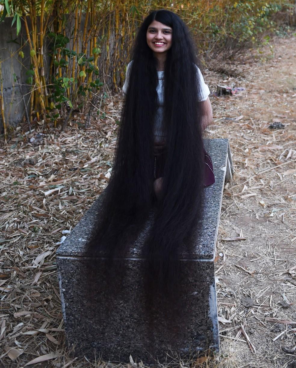 Nilanshi Patel, de 17 anos, exibe seus cabelos com 1,90 m de comprimento, que garantiram que ela fosse incluída no Livro Guinness dos Recordes, em Modasa, na Índia, no domingo (19) — Foto: Sam Panthaky/AFP