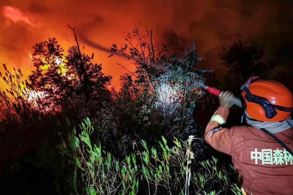 Bombeiro atua no combate a um incêndio florestal em Xichang, na província de Sichuan, no sudoeste da China (31) — Foto: STR/AFP