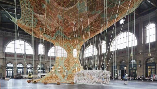 Escultura interativa feita de crochê, de autoria do carioca Ernesto Neto, em exposição na estação central de Zurique (Foto: MARK NIEDERMANN/FONDATION BEYELER/BBC)