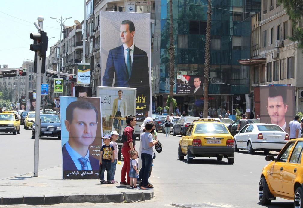 Sírios esperam para atravessar a rua em Damasco perto de cartazes do presidente da Síria, Bashar Al-Assad, em 18 de maio, dias antes da eleição presidencial — Foto: Firas Makdesi/Reuters