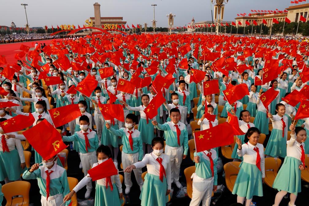 Participantes balançam bandeiras da China e do Partido Comunista durante evento na Praça Tiananmen, em Pequim, para relembrar os 100 anos do partido nesta quinta (1º) — Foto: Carlos Garcia Rawlins/Reuters