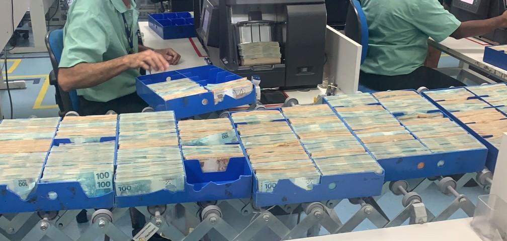 Dinheiro apreendido na casa de Glaidson sendo contabilizado — Foto: Reprodução