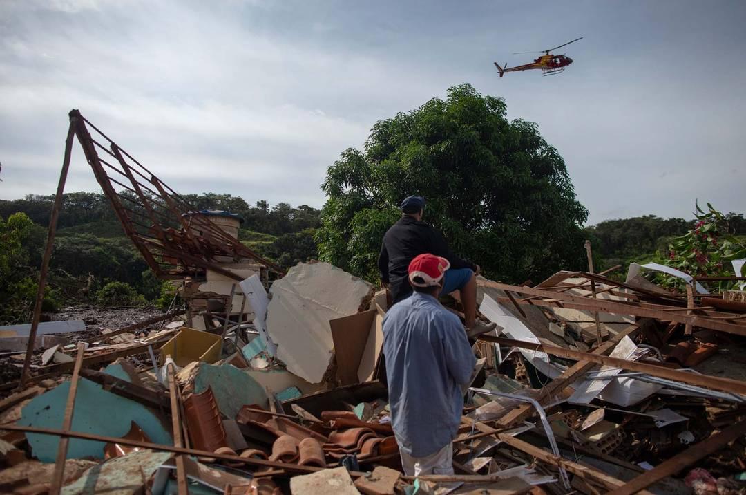Moradores do Parque da Cachoeira, em Brumadinho (MG) observam passagem de helicóptero.