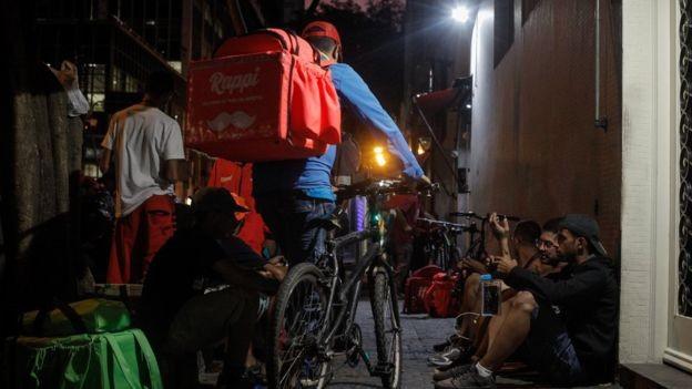 Na região da rua Augusta, centro de São Paulo, entregadores de aplicativos aguardam pedidos em calçada (Foto: LINCON ZARBIETTI, via BBC News Brasil)