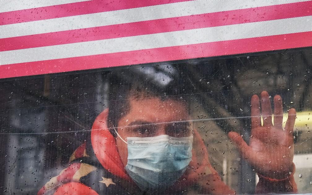 Homem com máscara acena da janela de um ônibus em Queens, Nova York, região que tem uma das maiores incidências de contágio por coronavírus nos EUA, na sexta-feira (3) — Foto: Spencer Platt/Getty Images/AFP