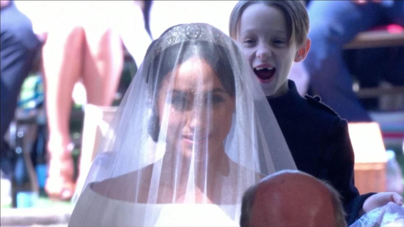 Um dos gêmeos sorri atrás de Meghan (Foto: Reprodução Youtube)