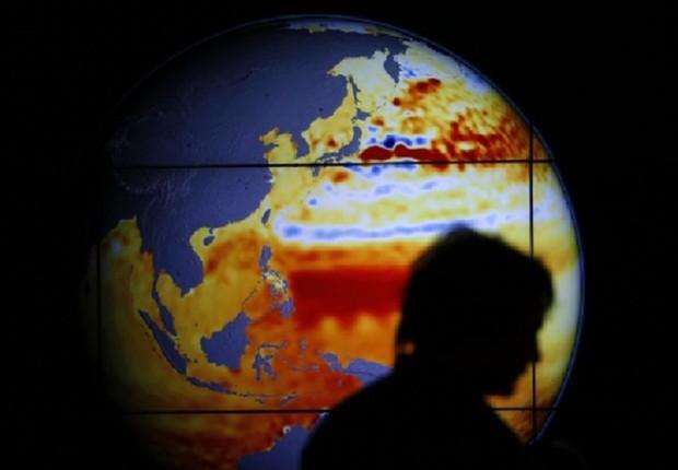 Mulher caminha diante de mapa que registra a elevação do mar nos últimos 22 anos durante a Conferência do Clima de Paris (COP21) (Foto: Stephane Mahe/Reuters)