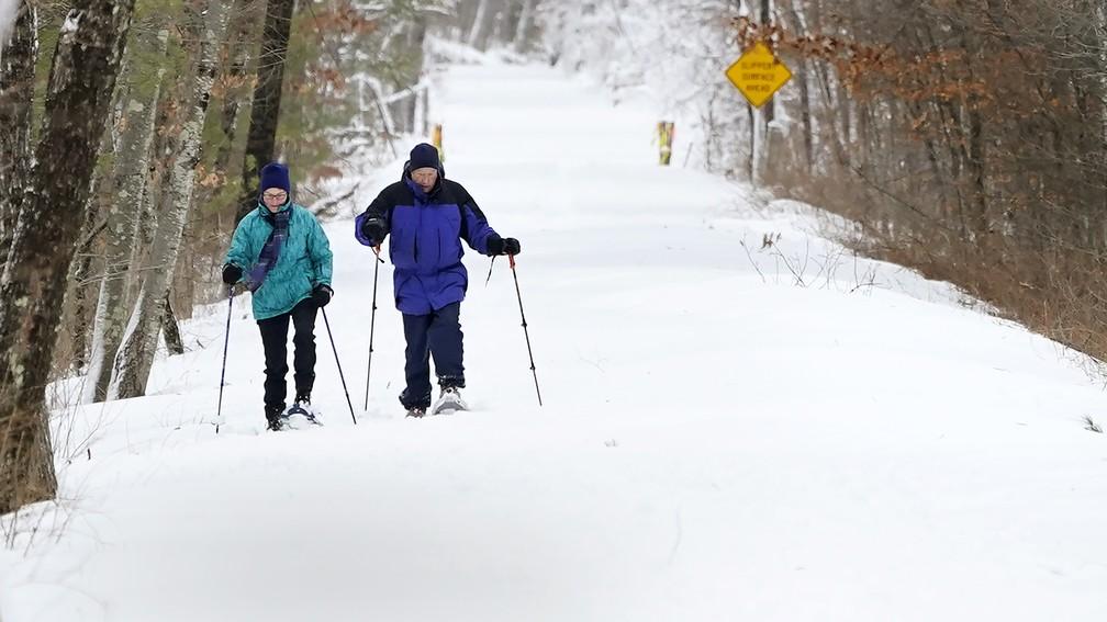 Casal caminha pela neve em New Hampshire depois da nevasca que atingiu a costa Leste dos EUA, em foto de 2 de fevereiro de 2021 — Foto: Charles Krupa/AP