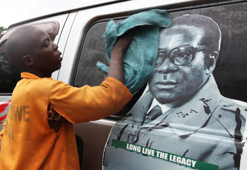 Jovem lava um ônibus com foto do presidente Robert Mugabe em um terminal em Harare — Foto: Philimon Bulaway / Reuters