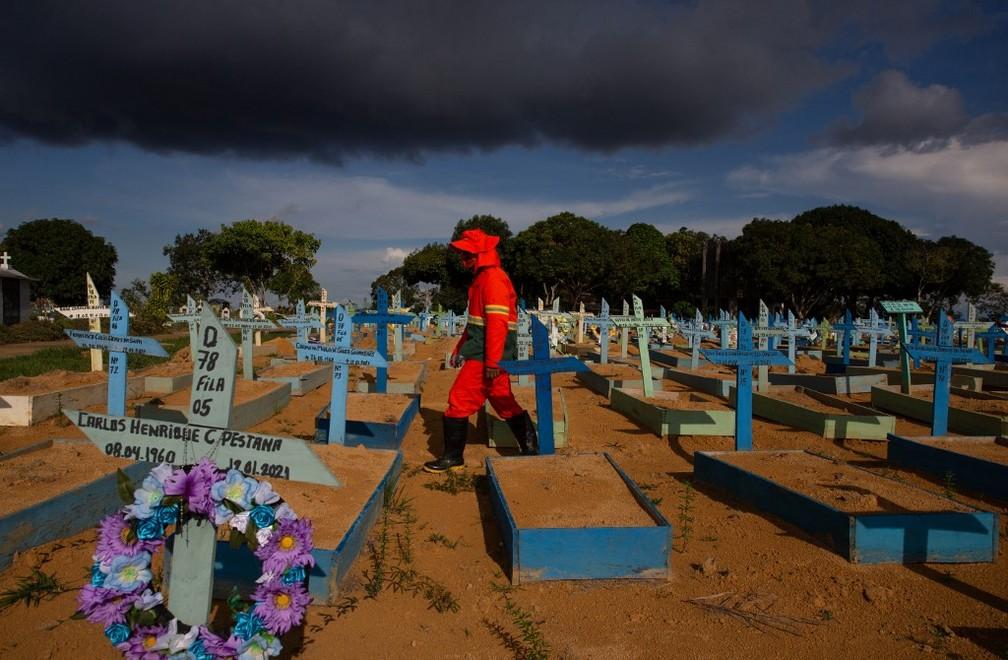 Coveiro anda em meio a túmulos de vítimas da Covid-19 no Cemitério Nossa Senhora Aparecida, em Manaus, no dia 30 de abril. — Foto: Michael Dantas / AFP