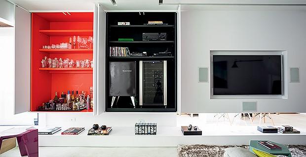Móvel multiuso | O armário embutido esconde a adega, o frigobar e os aparelhos eletrônicos na parte pintada de preto e as taças e bebidas na que recebeu tinta laranja. Nos dois nichos, é possível recolher as portas  (Foto: Edu Castello)