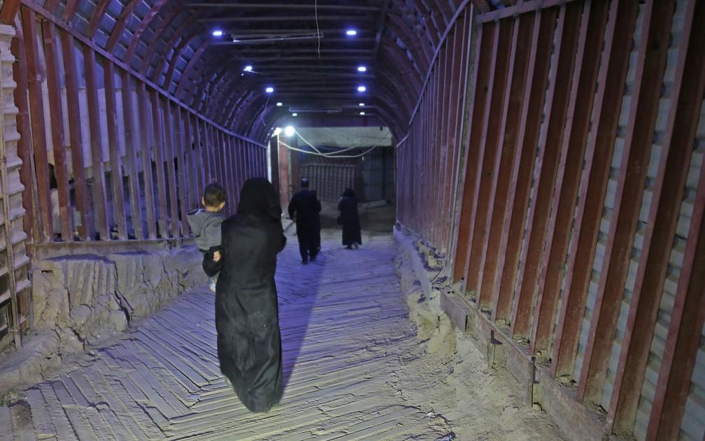 Pessoas caminham por túneis construídos por rebeldes na cidade de Duma, na Síria, na terça-feira (17) (Foto: Stringer/AP)