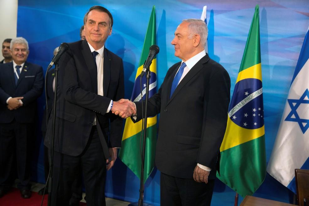O presidente Jair Bolsonaro e o premiê israelense Benjamin Netanyahu apertam as mãos após pronunciamento em Jerusalém — Foto: Heidi Levine/Pool/Reuters