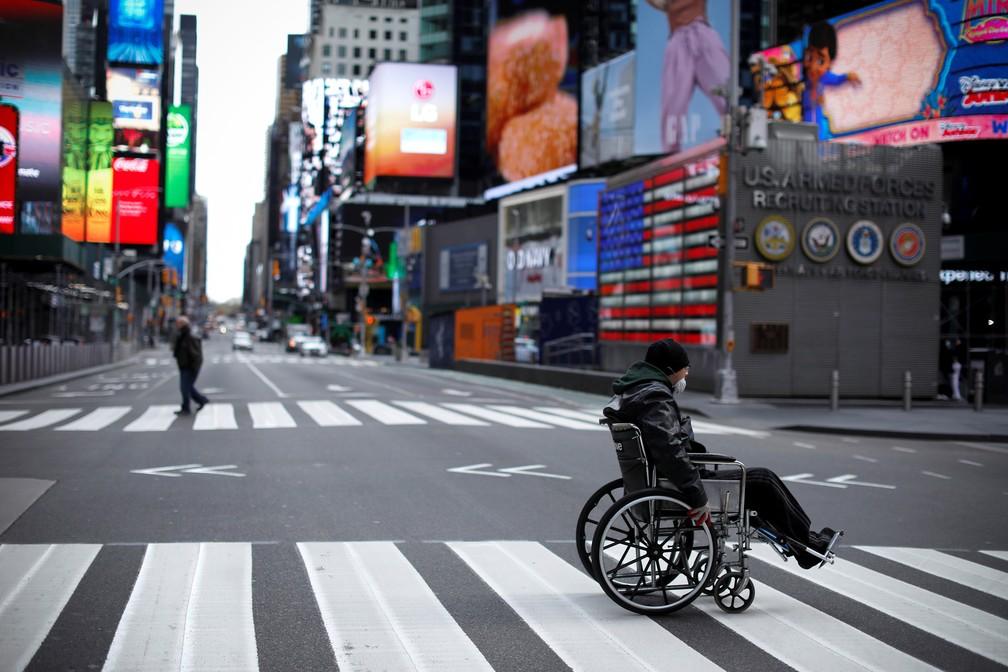7 de abril - Um homem em cadeira de rodas atravessa a 7ª Avenida quase vazia na Times Square, em Manhattan, Nova York, nesta terça-feira (7) — Foto: Mike Segar/Reuters