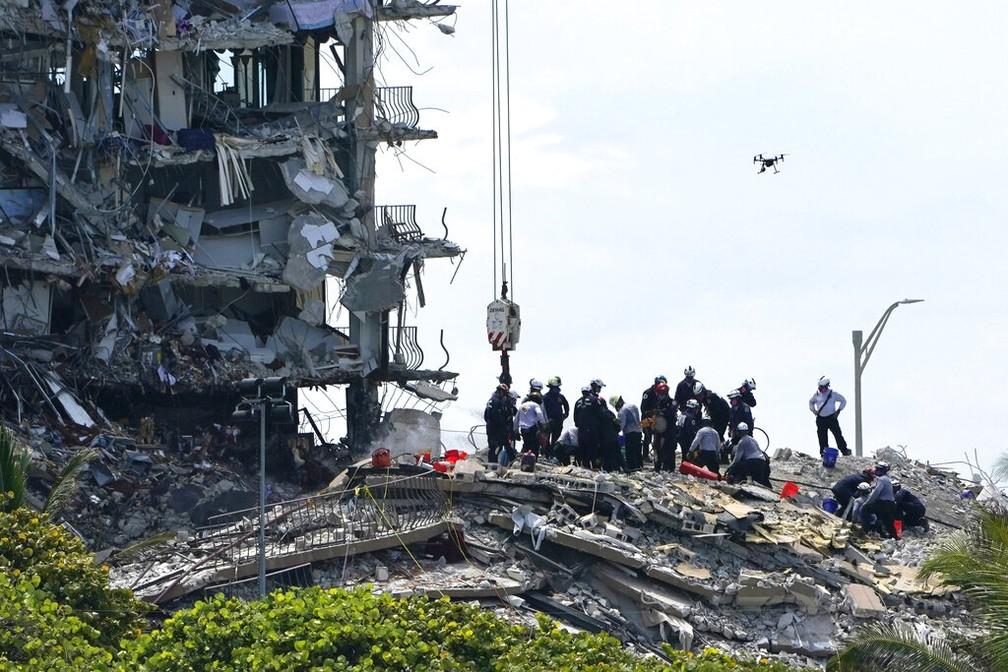Equipes de resgate procuram sobreviventes após desabamento do Champlain Towers South, em Surfside, na região de Miami, neste sábado (26) — Foto: Lynne Sladky/AP Photo
