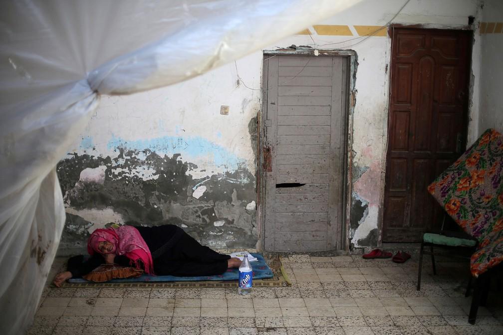 3 de janeiro - Mulher palestina descansa em sua casa no campo de refugiados de Khan Younis, no sul da Faixa de Gaza (Foto: Ibraheem Abu Mustafa/Reuters)