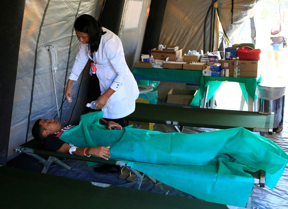 Profissional da secretaria da Saúde atende paciente com suspeita de dengue em tenda de hospital de campanha, no DF — Foto: Breno Esaki/Saúde-DF