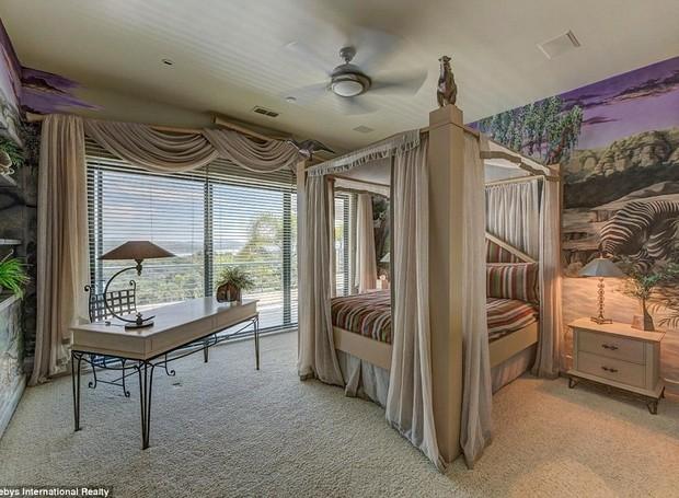 A decoração de um dos quartos da casa inclui uma parede com uma paisagem natural exótica pintada