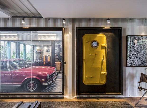 Uma porta de escotilha pintada de amarelo dá acesso ao elevador de carros (Foto: Maíra Acayaba)