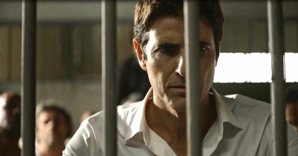 Régis (Reynaldo Gianecchini) é levado para uma cela lotada, na novela 'A Dona do Pedaço' — Foto: Globo