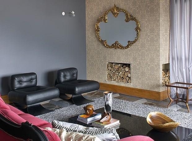 A sala decorada pelo designer Marcelo Rosenbaum tem papel de parede adamascado dourado em torno da lareira. A moldura do espelho também leva o tom (Foto: João Ribeiro/Editora Globo)