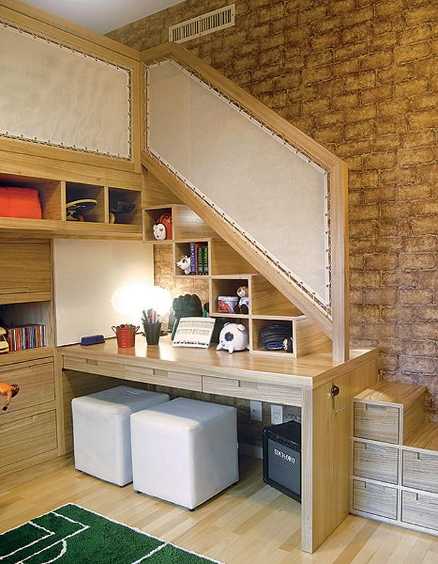 A solução para este quarto de irmãos foi suspender uma das camas, com projeto da designer de interiores Paola Ribeiro. Posicionada debaixo da escada, cujos interiores dos degraus são nichos para objetos, a escrivaninha é compartilhada pelos meninos (Foto: Celia Weiss/Divulgação)