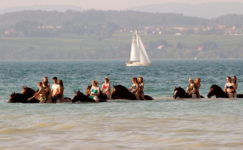Banhistas cavalgam dentro da água do Lago Constança, perto de Güttingen, na Suíça. País também foi atingido por onda de calor neste verão europeu (Foto: Reuters/Arnd Wiegmann )