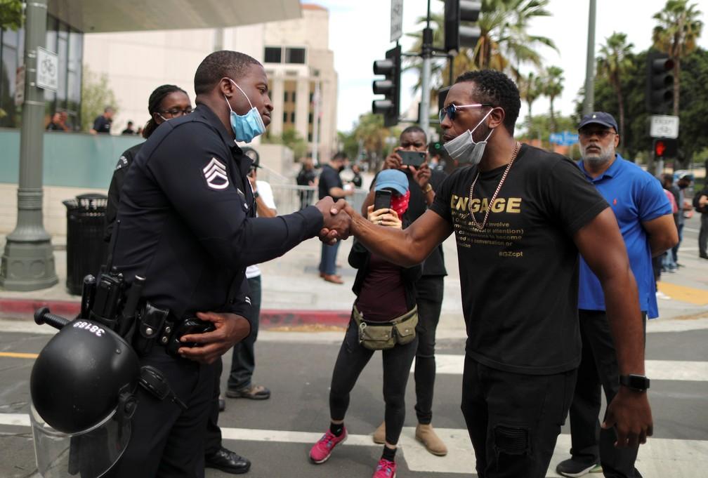 Um policial aperta a mão de um manifestante durante um protesto contra a morte de George Floyd do lado de fora da sede da polícia de Los Angeles, nos EUA, na terça-feira (2) — Foto: Lucy Nicholson/Reuters