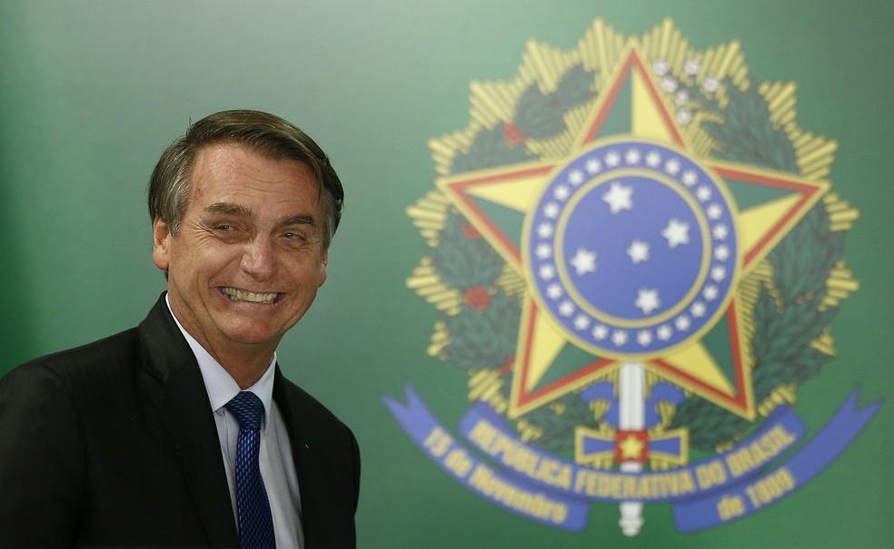 Jair Bolsonaro sorri ao lado do brasão da República — Foto: Dida Sampaio / Estadão Conteúdo