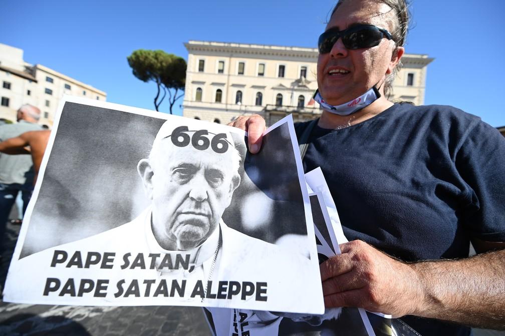 Manifestante antimáscaras leva cartaz que chama o Papa de 'satânico' — Foto: Vincenzo Pinto/AFP