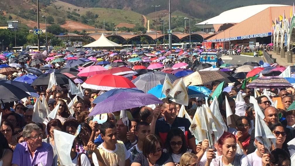 Sob forte sol, fiéis disputam espaço no guarda-chuva para acompanhar a missa  (Foto: Carlos Santos/G1)