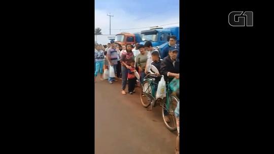 Moradores fazem fila para receber leite que seria jogado fora por produtores de Ouro Verde do Oeste; VÍDEO