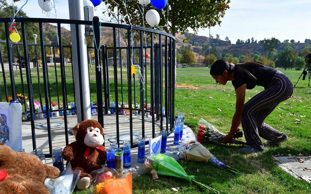 Mulher deposita flores em memorial na frente da escola Saugus, onde jovem matou duas pessoas e feriu outras três a tiros, na sexta-feira (15)  — Foto: Frederic J. Brown/AFP