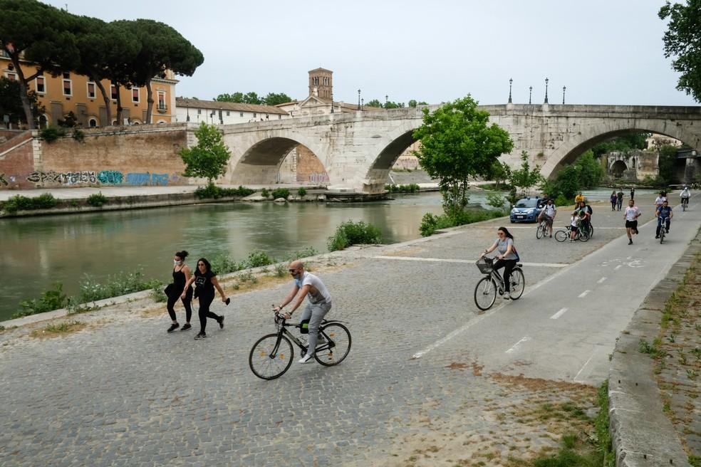 Pessoas andam de bicicleta em uma ciclovia ao longo do rio Tibre no centro de Roma, na Itália. — Foto: Andreas Solaro/AFP
