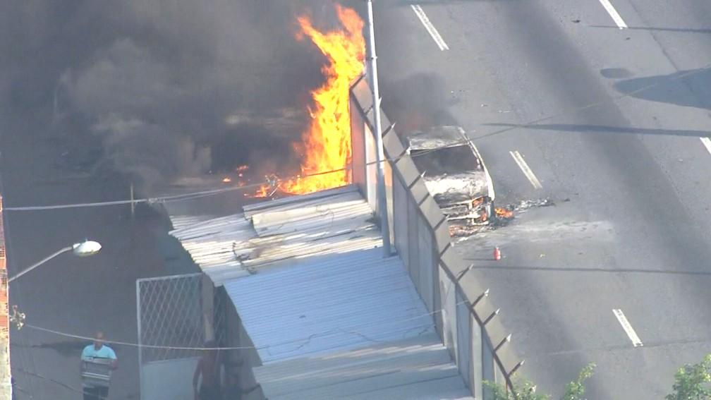 Carro pega fogo na Linha Vermelha; no canto inferior esquerdo da imagem, pessoas tentam retirar pertences dos barracos — Foto: Reprodução/TV Globo