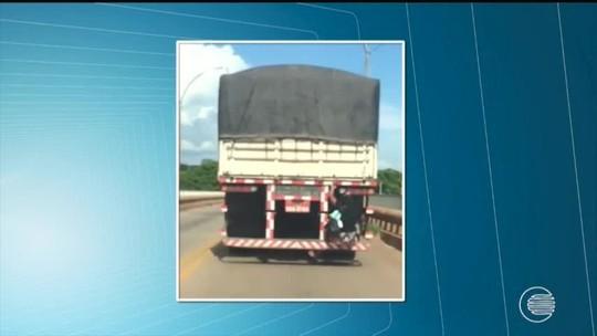 Mulher é flagrada atravessando ponte pendurada em carroceria de caminhão em Teresina