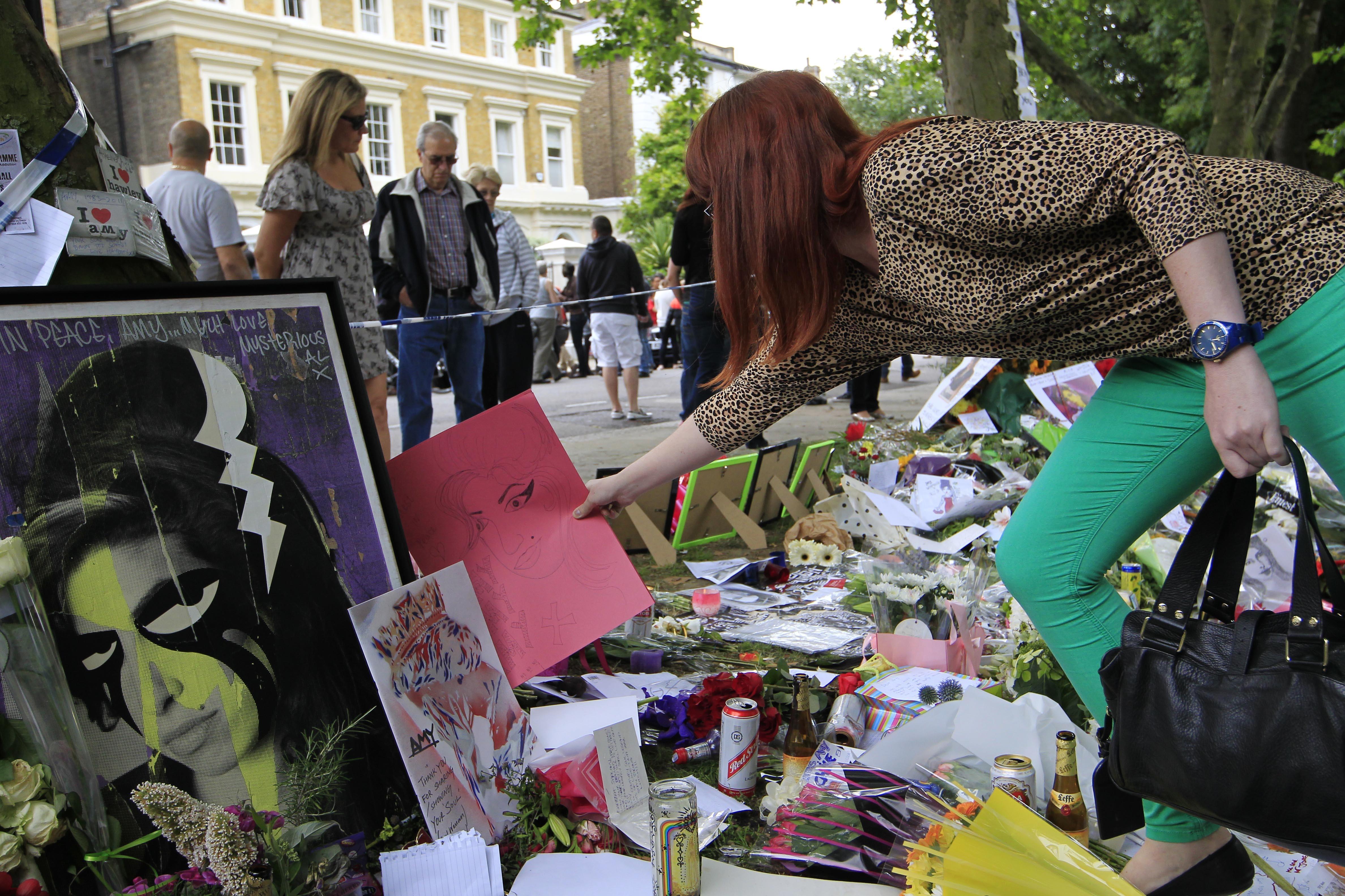 Uma fã coloca um desenho entre as flores e homenagens deixadas para a cantora britânica Amy Winehouse, fora de sua casa em Londres