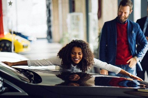 Young woman and her husband in the showroom purchasing new car (Foto: Getty Images)