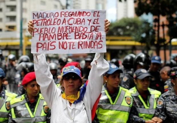 Em Caracas, manifestante da oposição culpa o presidente Maduro por ajudar países aliados enquanto os venezuelanos morrem de fome  (Foto: Reuters via BBC)