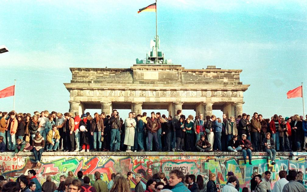Foto de arquivo mostra cidadãos da Alemanha Ocidental ainda em vigília em cima do Muro de Berlim em frente ao Portão de Brandemburgo na manhã do dia seguinte à queda, em 10 de novembro de 1989 — Foto: Arquivo/Reuters