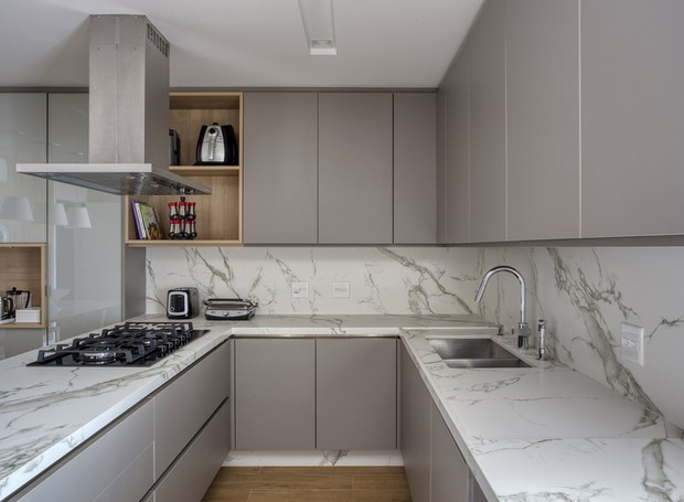 O ultrarresistente Dekton foi escolhido para a bancada, frontão e rodapés da cozinha, que tem porcelanato no piso. Os armários da Florense alternam MDF e vidro nas portas em tom de cinza (Foto: MCA Estúdio/Divulgação/Produção: Núria Uliana)