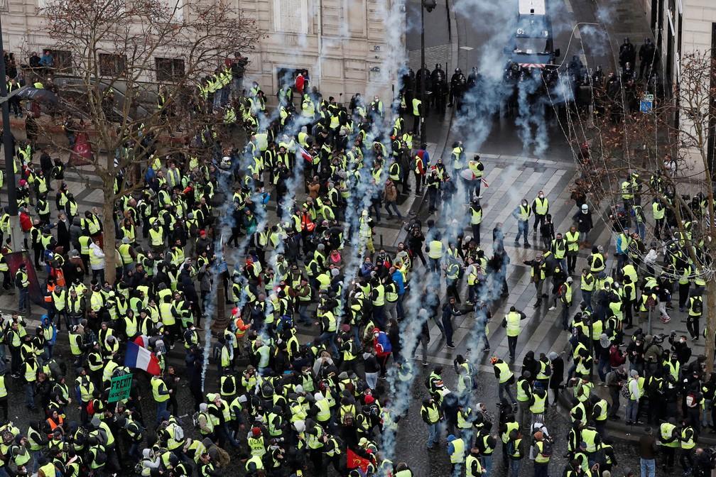 Polícia atira bombas de gás lacrimogêneo em manifestantes na Champs Elysees, em Paris — Foto: Benoit Tessier/Reuters